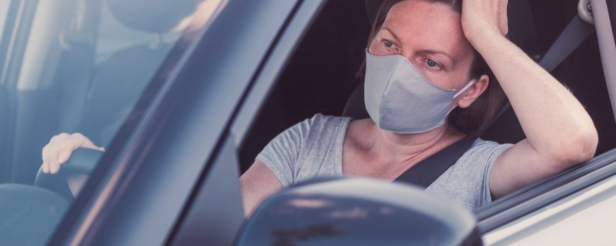 Bored woman with protective face mask waiting in the car
